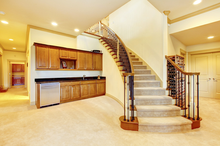 Large bright hallway interior design. Nice basement staircase with metal railing and beige carpet.