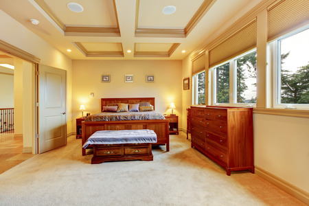 Luxurious creamy bedroom with wooden bed, vanity cabinet, trimmed ceiling, carpet floor. Stock Photo