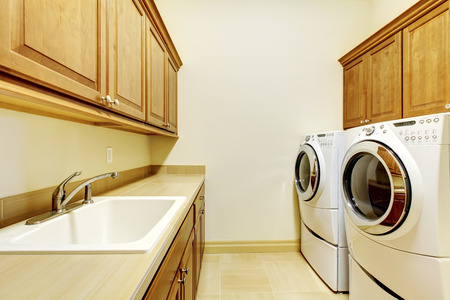 laundry room: Luxury laundry room with wood cabinets and white washer and dryer.