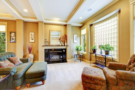 living room window: Beautiful living room with large window,  fireplace and trimmed ceiling. Lots of decor.