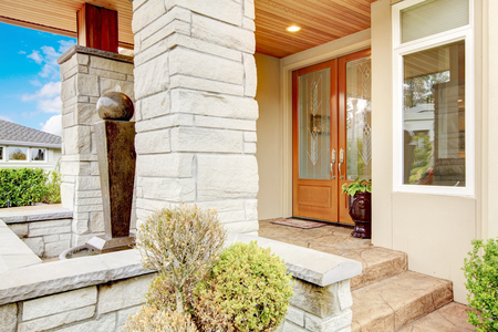 Luxury house entrance porch with stone column trim, stained wood door and window.