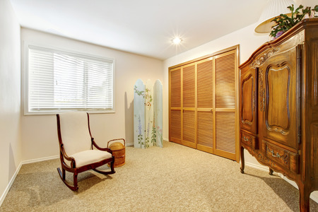 guest room: Guest room with armore , closet doors and chair.