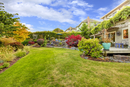 yard: Large fenced backyards with fall landscape and view of the deck. Stock Photo