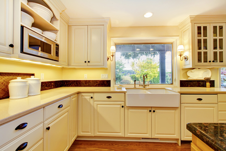 white trim: Cream color kitchen with large white sink and classic design.