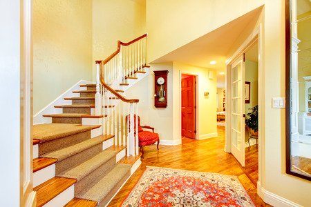 Beautiful luxury home entrance hallway with large staurcase and red door. Stock Photo