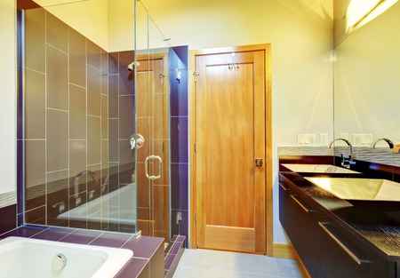 screened: Cherry brown bathroom interior with glass screened shower, cabinets and tub Stock Photo