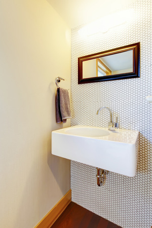 framed: White hand wash basin in the corner with framed mirror Stock Photo