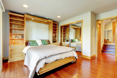 polished floor: Bright bedroom with storage combination, sliding-door mirror wardrobe and polished hardwood floor Stock Photo