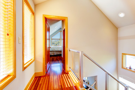 cherry hardwood: Small modern hallway with metal railings and cherry hardwood floor.