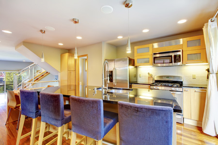kitchen counter top: Cozy bright kitchen with    granite counter top, kitchen island, blue wooden stools and steel appliances Stock Photo