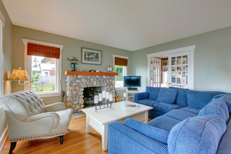classic living room: Classic American living room with comfortable blue sofa and fireplace decorated with stone.