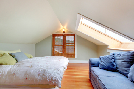 vaulted ceiling: Upstairs small bedroom with vaulted ceiling,  blue sofa and hardwood floor. Stock Photo