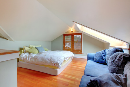 vaulted ceiling: Small bedroom in the attic with vaulted ceiling and hardwood floor.