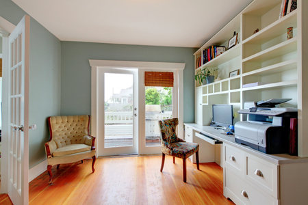home office interior: Home office with white open shelves, hardwood floor and blue walls.