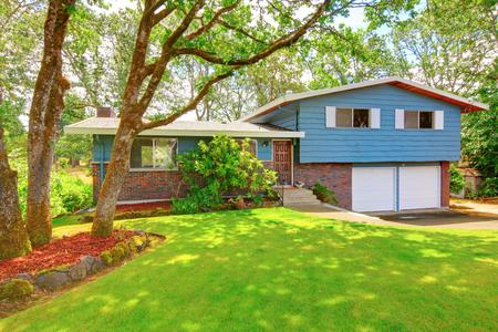 rambler: Small brick American rambler exterior with double doors garage and nice front garden.