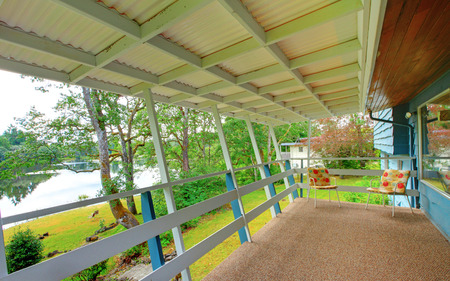 home and garden: Backyard covered deck with carpet floor and two chairs overlooking water view.