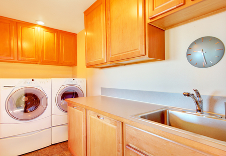 dryer  estate: Laundry room with modern appliances and light tone wooden cabinets. Stock Photo