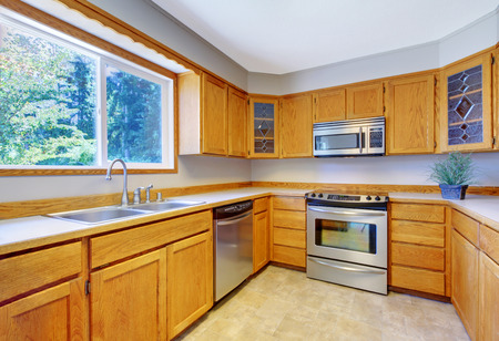 cabinets: Bright kitchen room interior with tile floor, light brown storage cabinets and stainless steel appliances.