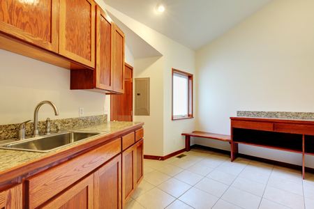 kitchen counter top: Bright kitchen room interior with brown wooden storage cabinets, granite counter top and tile floor. Stock Photo