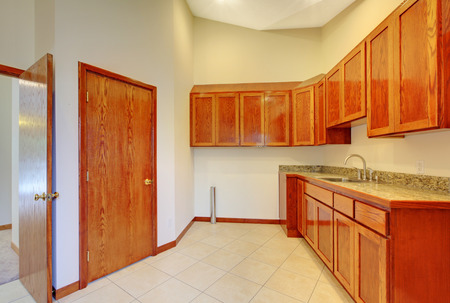 kitchen cabinets: Small kitchen room interior with brown wooden storage cabinets, tile floor and beige walls.