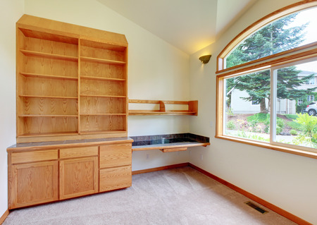 trim wall: Empty room interior with beige carpet, cabinet and large window with brown trim. Stock Photo