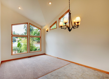 vaulted ceiling: Empty room interior in beige tones with large window, chandelier, carpet floor  and vaulted ceiling. Stock Photo