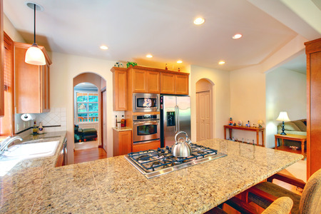 kitchen counter top: Bright kitchen room interior with brown cabinets, granite counter top and stainless steel appliances. Stock Photo