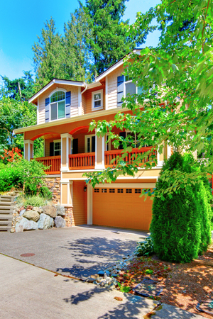 three story: Adorable orange three story house with driveway, concrete walkway and lots of greenery. Stock Photo