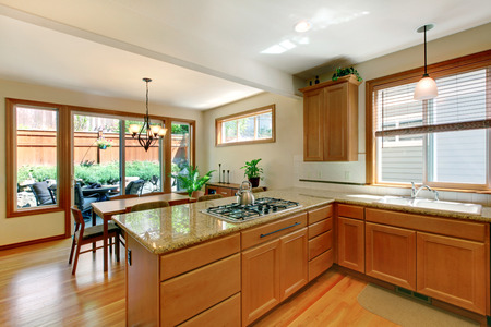 kitchen cabinets: Brown and white kitchen room with hardwood floor, cabinets, granite counter top. Kitchen room open to cozy dining area. View of back yard. Stock Photo