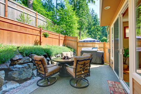 concrete floor: Fenced backyard patio area with table set and concrete floor. Stock Photo