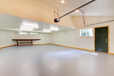 vaulted ceiling: Spacious empty garage interior with green door, small window and vaulted ceiling.
