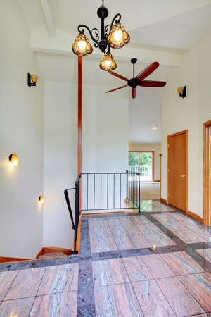 upstairs: Bright upstairs hallway with tile floor, high white ceiling and staircase. Stock Photo