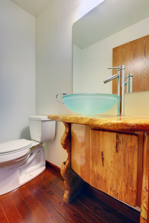 vessel sink: White and brown bathroom with wooden cabinet, modern glass vessel sink and hardwood floor.