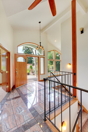 way of living: Nice bright entry way to home with high vaulted ceiling, tile floor, staircase and large window.