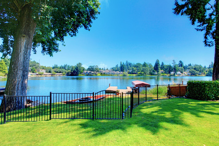 garden styles: Backyard area with well kept lawn and black metal fence. Beautiful water view Stock Photo