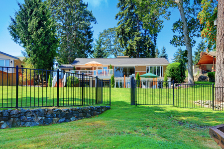 back yard: House exterior. Back yard with the large house with metal fence and green lawn.