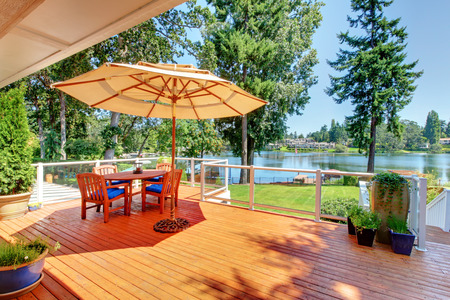 home and garden: Sitting room area on walkout deck with patio table, umbrella and chairs overlooking water view.