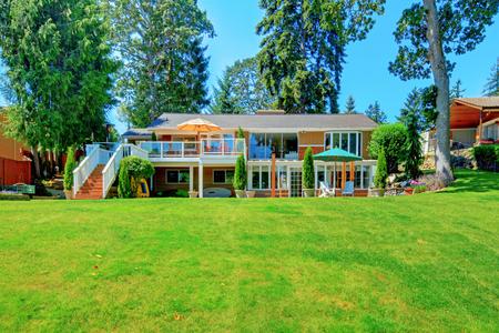 House exterior with impressive backyard landscape design and cozy patio area. Reklamní fotografie