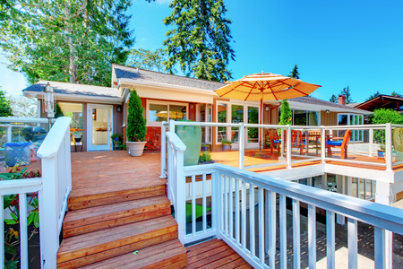 screened: House exterior. Cozy screened walkout deck with patio area and white railings staircase.