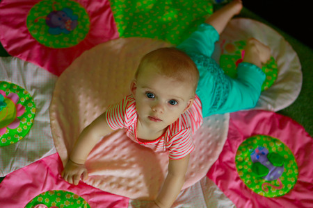 girl looking up: Cute baby with blue eyes looking up from colorful rug Stock Photo