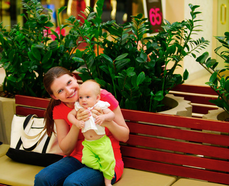 mother on bench: Family shopping. Young mother and her daughter on the bench. Mother with baby girl with shopping bags with mall on background.