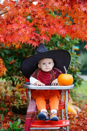 eating fruits: Halloween holiday. little girl blonde in a black hat sitting at a table next to a pumpkin in the garden Stock Photo