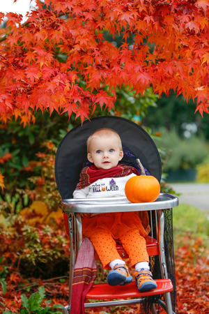 Halloween holiday. little girl blonde in a black hat sitting at a table next to a pumpkin in the garden Stock Photo