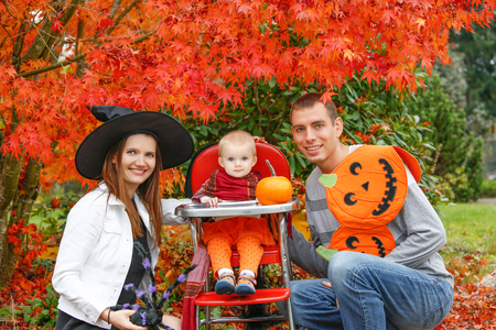 Halloween holiday. little girl blonde in a black hat sitting at a table next to a pumpkin in the garden with parents