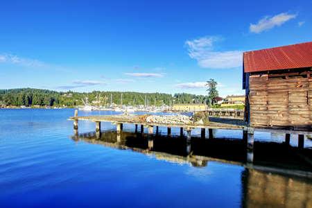 in wa: Gig Harbor, WA - September 25, 2011: Small town downtown marina area. Blue sky Editorial