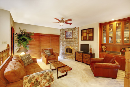 stone fireplace: Cozy upstairs living room interior in brown tones with stone fireplace in the corner and built-in cabinet. Stock Photo