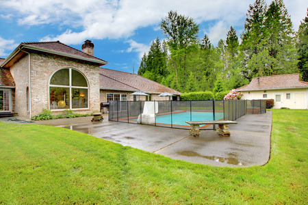 lawn area: Luxurious northwest home with large pool and patio area. View of shed and green lawn.