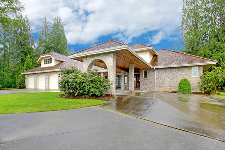 curb appeal: Beautiful curb appeal after rain. Large brick house with three garage spaces and driveway with arch.