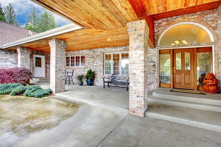 Porche d'entrée Cozy d'une grande maison de briques. zone Patio avec plancher de briques et colonnes de béton. Vue de vitrail porte en bois. Banque d'images - 59591663