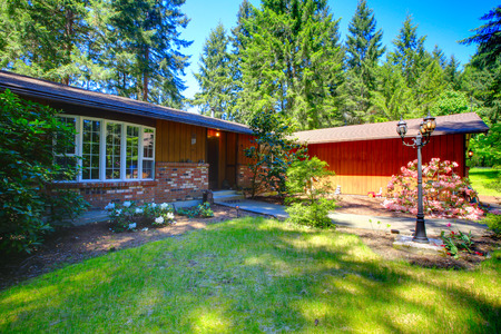 American rambler house exterior. View of walkway with flower bed and green lawn. Reklamní fotografie